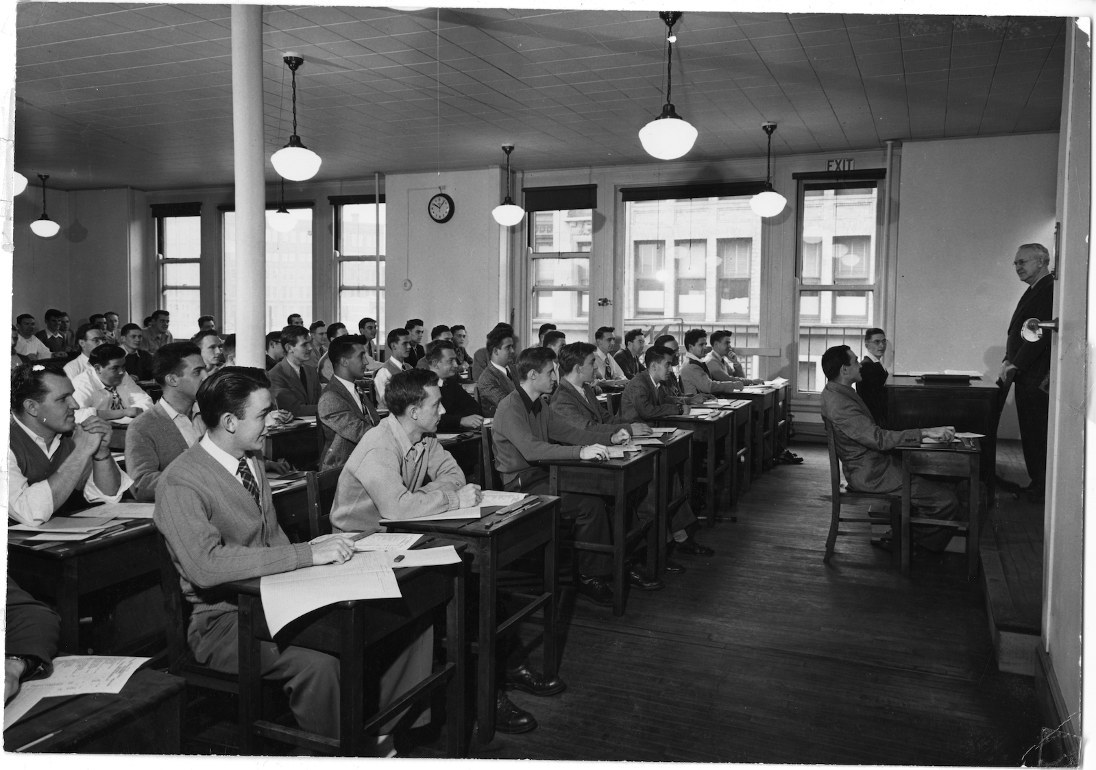 A group of male students, seated at desks in a classroom, presumably in one of the Boylston Street buildings on the Boston campus.